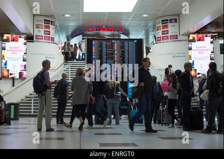 passengers looking at the departures board at Gatwick airport north terminal - Stock Photo