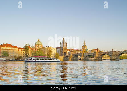 Charles Bridge of Prague with a boat on river Vltava - Stock Photo