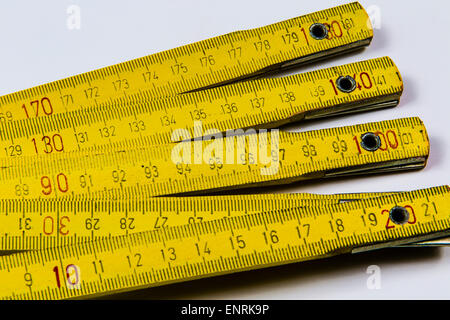 Yellow wooden folding ruler on white background - Stock Photo