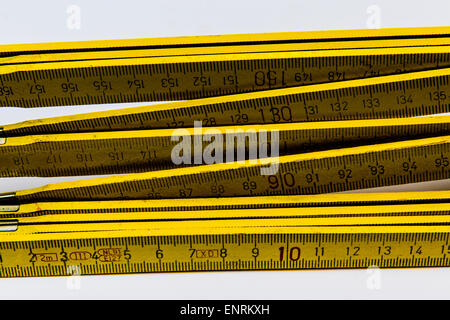 Yellow wooden folding ruler on white background - Stock Photo