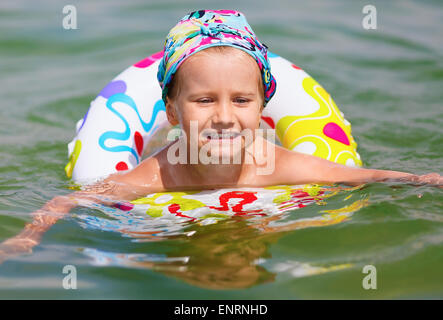 Baby bathing in the sea and floats on inflatable ring. Shallow depth of field. Selective focus on the model's face. - Stock Photo