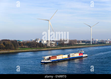 A container barge  sailing into the port of Rotterdam, Netherlands, with windmills in the background