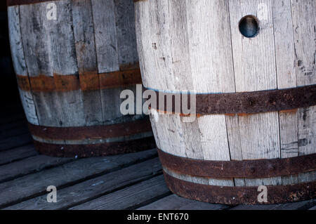 Two old, wooden barrels on a barn floor - Stock Photo