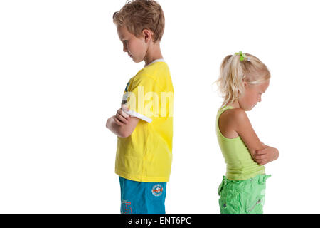 Portrait of blond sister and brothe in a quarrel standing with their back to each other on white  background with - Stock Photo
