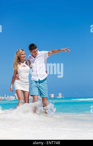 Romantic couple walking on perfect beach with turquoise sea, enjoying life and each other at honeymoon vacation. - Stock Photo