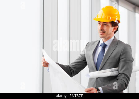 businessman in construction helmet with blueprints - Stock Photo