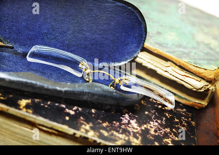 Pince-nez in a metallic case on old books - Stock Photo