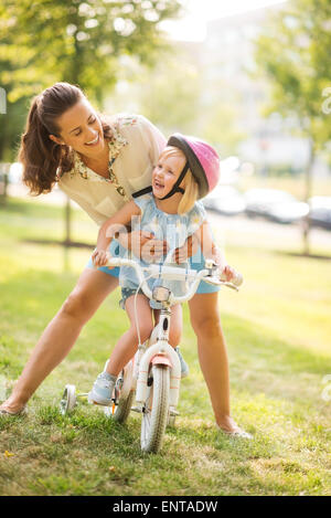 A mother hugs her daughter from behind, as the daughter wearing a pink helmet looks up towards her mother, laughing - Stock Photo