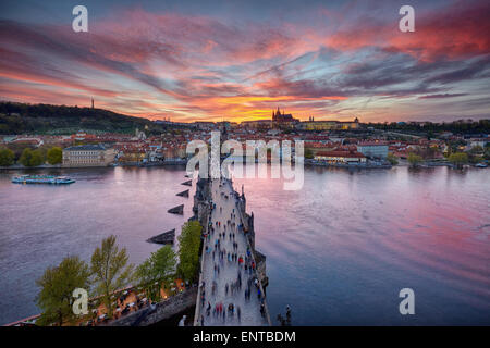 sunset over Charles Bridge and Prague Castle - Stock Photo