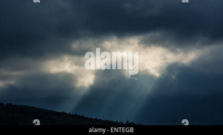 Sun rays break through the clouds in a dramatic stormy sky, UK - Stock Photo
