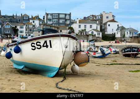 Fishing boats at low tide stranded on the beach in the harbour, St Ives, Cornwall, England, UK - Stock Photo