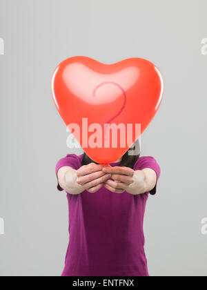 caucasian woman holding heart shaped balloon with question mark in front of her head, against grey background - Stock Photo