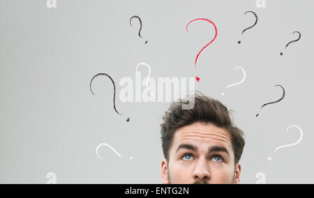 thinking man with many question marks above his head, against grey background - Stock Photo