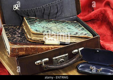Old books, ivory cigarette holder, key and pince-nez in a retro suitcase - Stock Photo