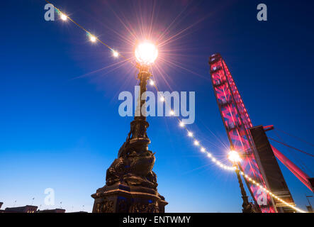 A lamp  and lights with strong flare on the South Bank, the London Eye is in the background - Stock Photo