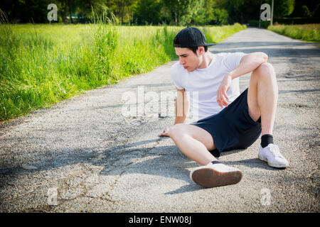 Handsome young man resting sitting on road after running and jogging in country in a sunny day - Stock Photo
