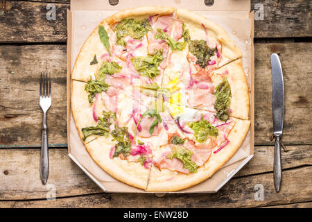 Fast food eating background. Pizza in carton box with silverware on wooden table. Top view image - Stock Photo