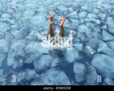 Cool down and Cooling off concept as a diver diving into frozen ice water as a symbol for managing hot weather summer - Stock Photo
