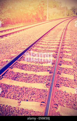 Vintage retro filtered picture of railroad tracks, old film effect applied. - Stock Photo