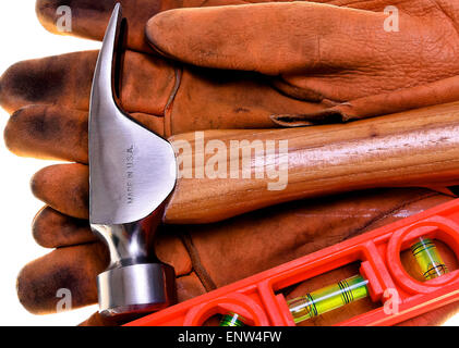 Closeup of new construction framing hammer and bubble level on heavy leather work gloves Made In America - Stock Photo