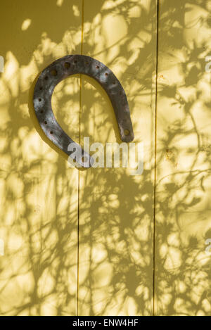 old horseshoe hanging on the wooden wall of a house - Stock Photo