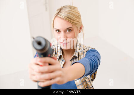 Home improvement - woman with battery screwdriver - Stock Photo