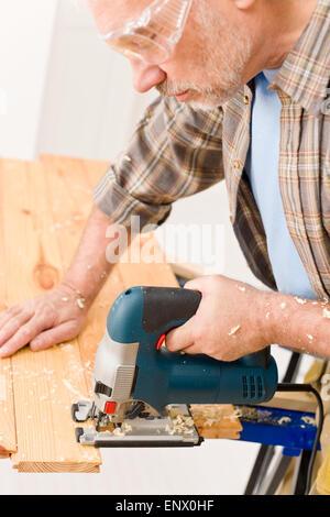 Home improvement - handyman cut wood with jigsaw - Stock Photo