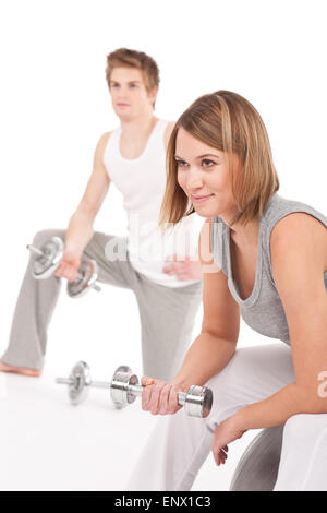 Young couple with weights and fitness ball on white - Stock Photo