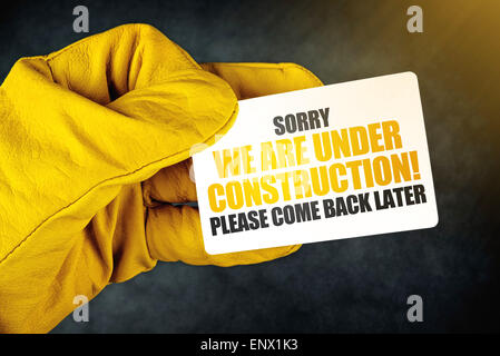 Under Construction on Business Card, Male Hand in Yellow Leather Construction Working Protective Gloves Holding - Stock Photo