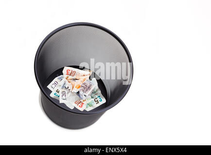 Sterling money pound notes pounds screwed up and thrown away in a wastepaper bin on white to illustrate wasting - Stock Photo