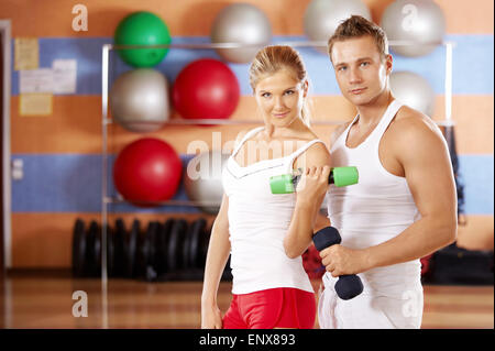 Pair of sportsmen with dumbbells in hands in sports club - Stock Photo