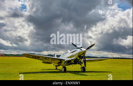 The gleaming metal bodywork of this Curtiss P-40C Warhawk sits under stormy skies at the Flying Legends Airshow, - Stock Photo