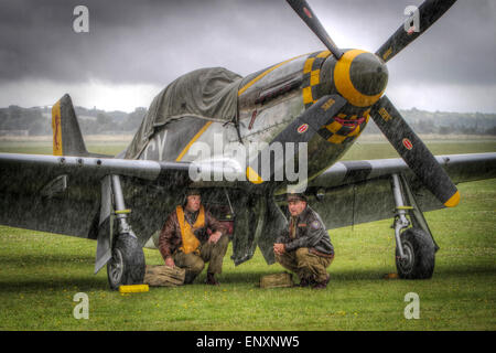 World War 2 re-enactors shelter beneath a P-51 Mustang during the Flying Legends show at RAF Duxford - Stock Photo