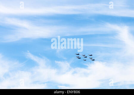flight of military low-flying aircrafts in white clouds in blue sky - Stock Photo