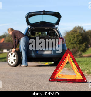 Das Rad am Auto wechseln - Stock Photo