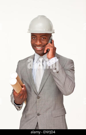 Attractive ethnic architect on phone holding plans - Stock Photo