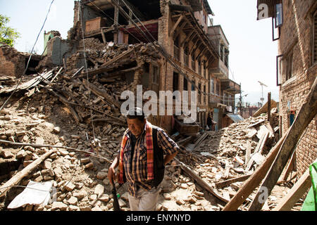 A man walks through the rubble of houses damaged by the earthquake in Sankhu Village near Kathmandu, Nepal. - Stock Photo