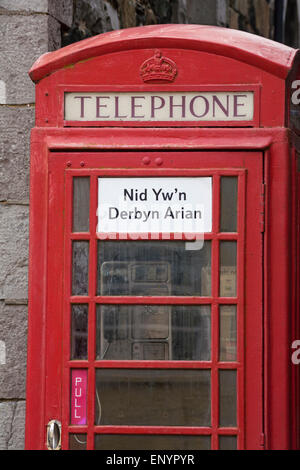 Red telephone box with sign in Welsh that it does not accept money, at Lower Fishguard or Abergwaun, Pembrokeshire, - Stock Photo