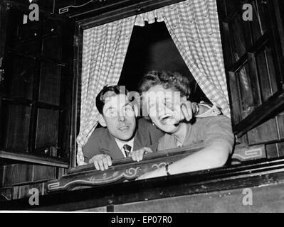 Ein junger Mann und eine junge Frau schauen fröhlilch aus dem Fenster eines Nachtclubs auf der Reeperbahn in Hamburg, - Stock Photo
