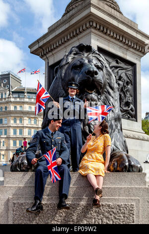A Group Of People Dressed In 1940's Period Clothing Wave Union Flags In Trafalgar Square, London, England - Stock Photo