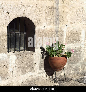 Geranium flowers in plant pot standing next to a small window in courtyard in Arequipa, Peru - Stock Photo