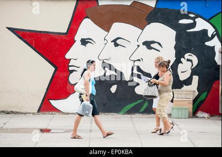 HAVANA, CUBA - JUNE 13, 2011: Cuban pedestirans walk in front of propaganda mural featuring three leaders of the - Stock Photo