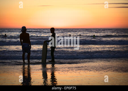 Young people standing on the shore on Cavancha beach at sunset in Iquique, Chile - Stock Photo