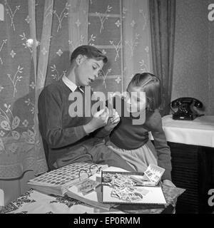 Ein Junge zeigt einem Mädchen seine Briefmarkensammlung, Deutschland 1950er Jahre. A boy showing a little girl his - Stock Photo