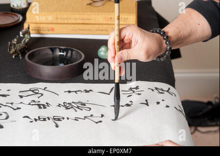 Man's hand using a brush to paint Chinese calligraphy on a large sheet of white paper in Gaithersburg, Maryland. - Stock Photo