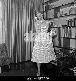 Eine junge Frau in einem Petticoat steht unter einem Bücherregal und telefoniert, Deutschland 1950er Jahre. A young - Stock Photo