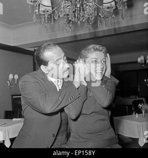 Ein Mann hilft einer jungen Frau in einem Restaurant, ihre Frisur zu richten, Deutschland 1950er Jahre. A man helping - Stock Photo