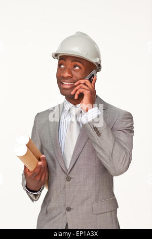 Smiling Afro-American architect speaking on mobile phone - Stock Photo