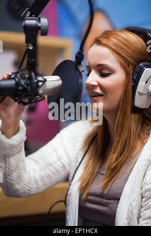 Portrait of a young radio host speaking - Stock Photo