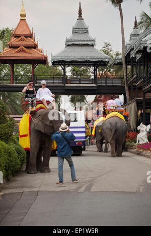 Tourists enjoy a ride on an elephant within the grounds of the famous Nong Nooch Gardens in Pattaya, Thailand - Stock Photo